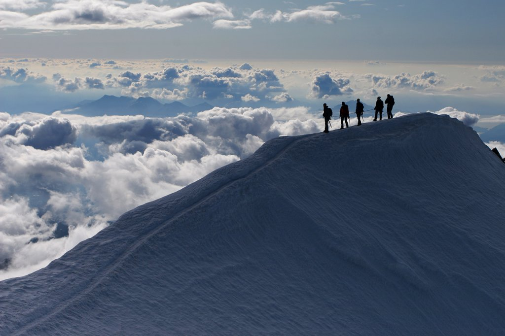 Climbers on top of snowy mountain - above the clouds